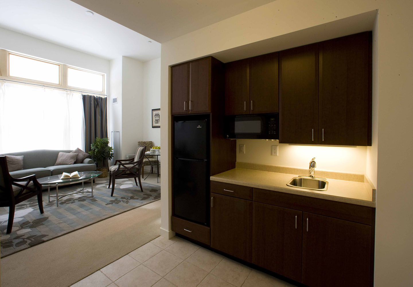 A kitchenette opens to a sunny living room in an assisted living apartment at NewBridge on the Charles.