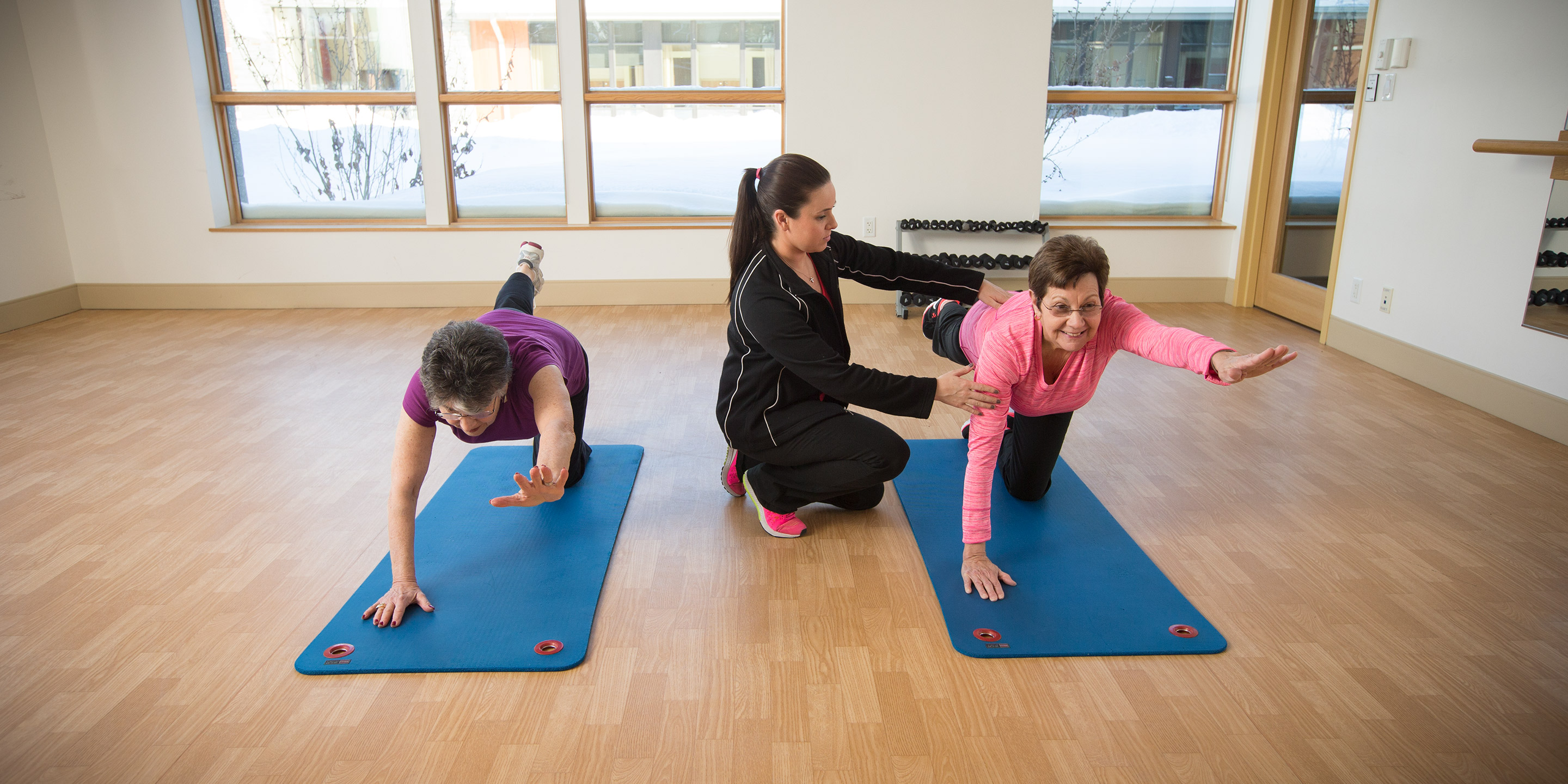 Two women do yoga poses while one gets help from an instructor