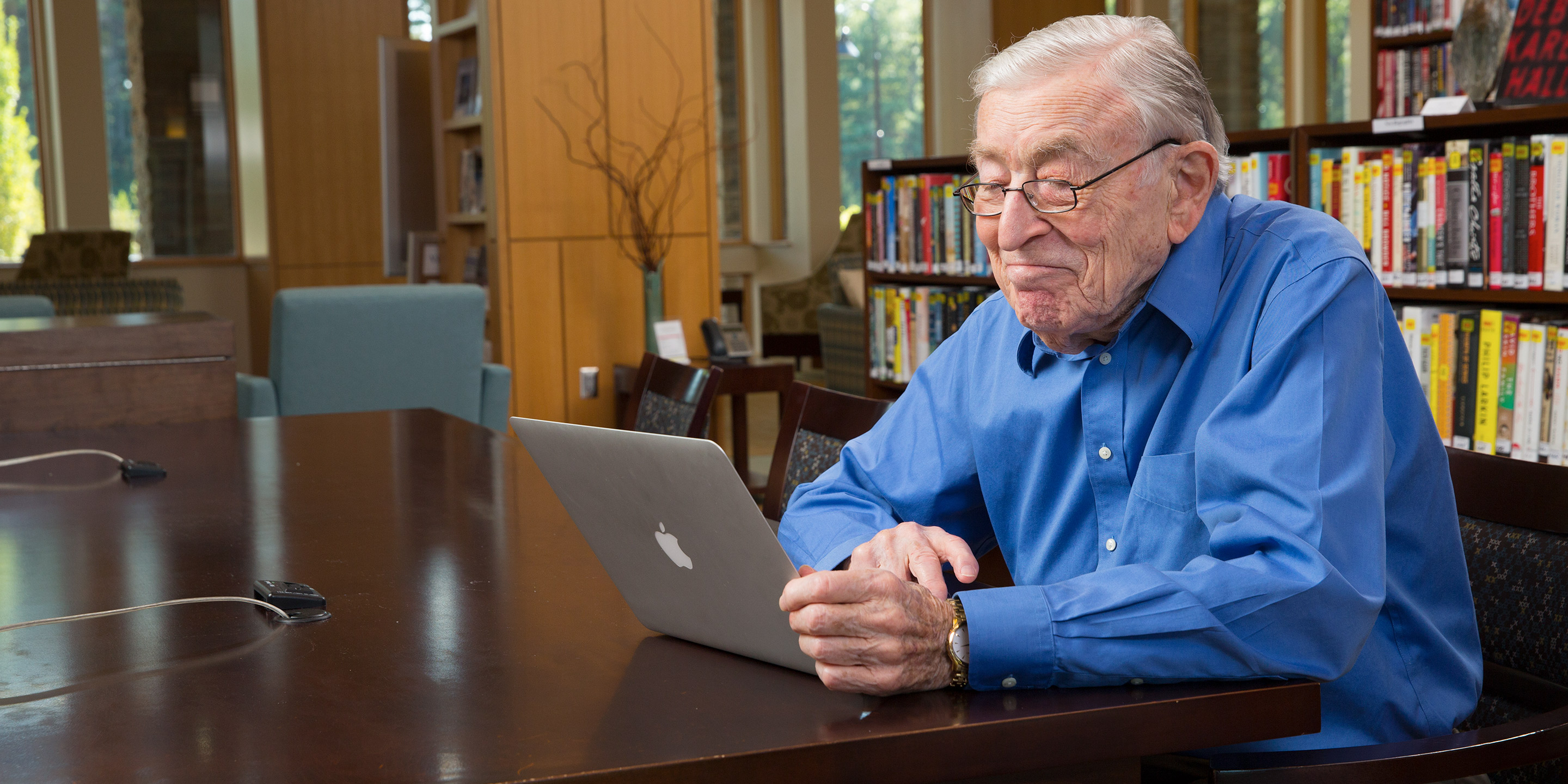 An elder male sits and smiles at a laptop while sitting in a library