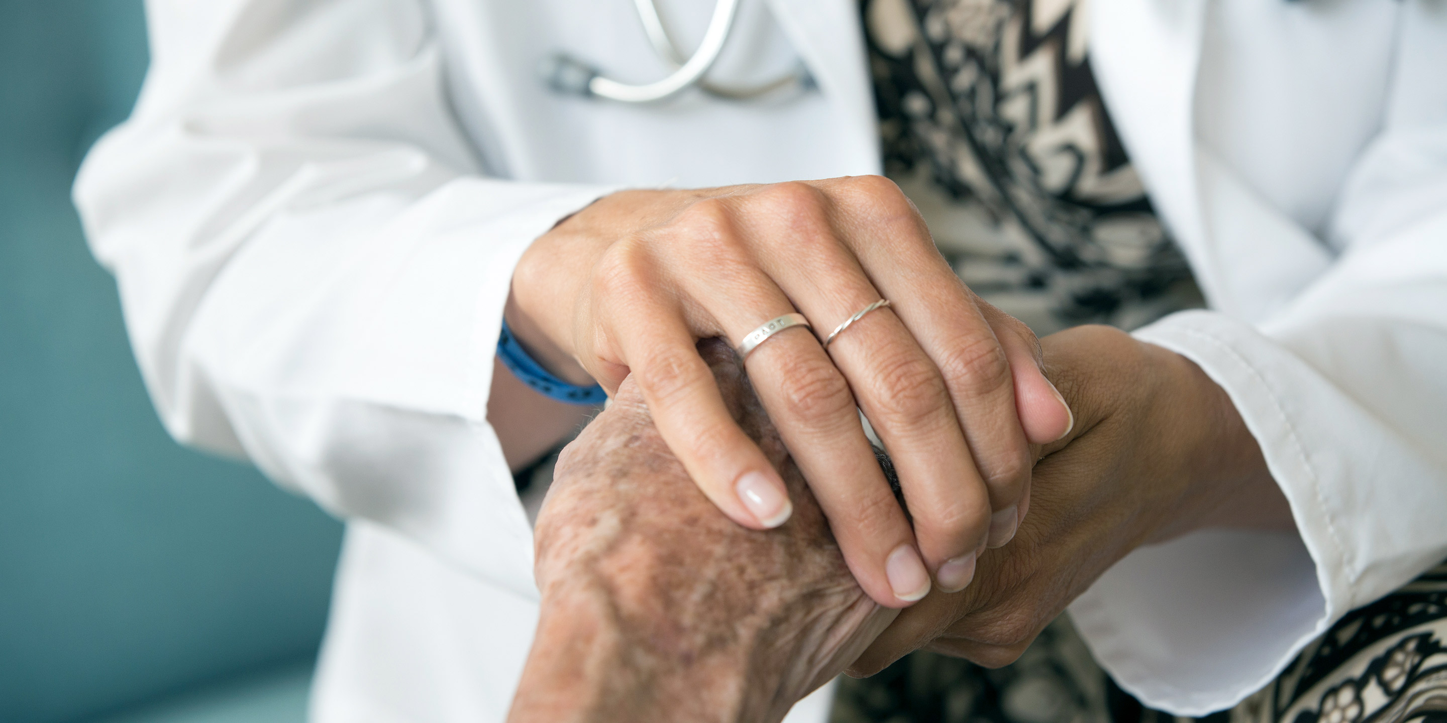 A female doctor wearing a white coat places her hand over a patient's hand