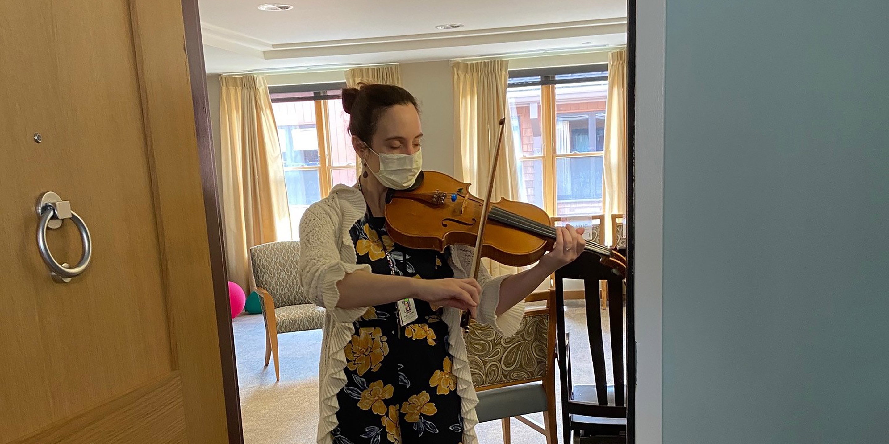 NewBridge on the Charles employee, Leticia Alvaraz, plays a violin while wearing a face mask during the COVID-19 coronavirus pandemic