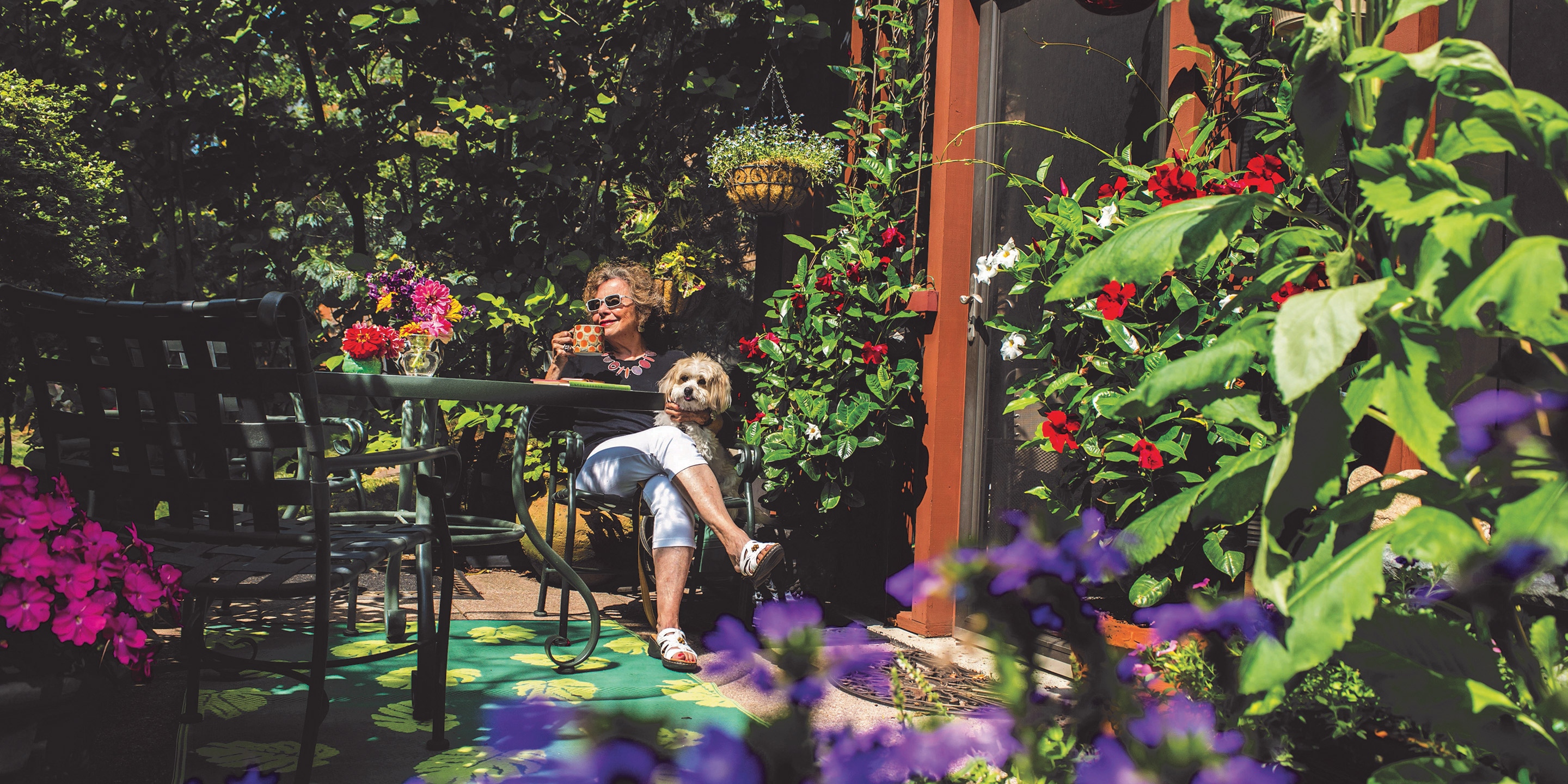 A female NewBridge resident sits in a garden with her dog.