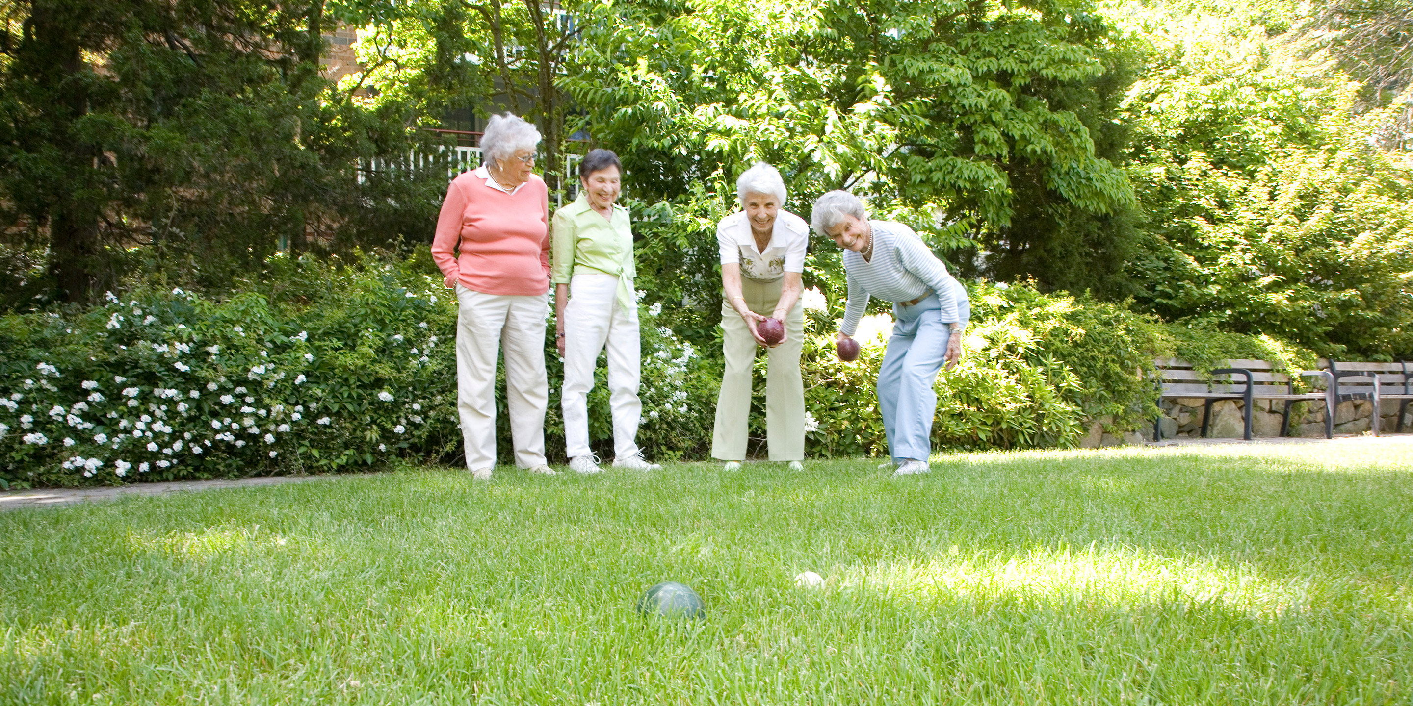 Four female residents play bocce ball outside