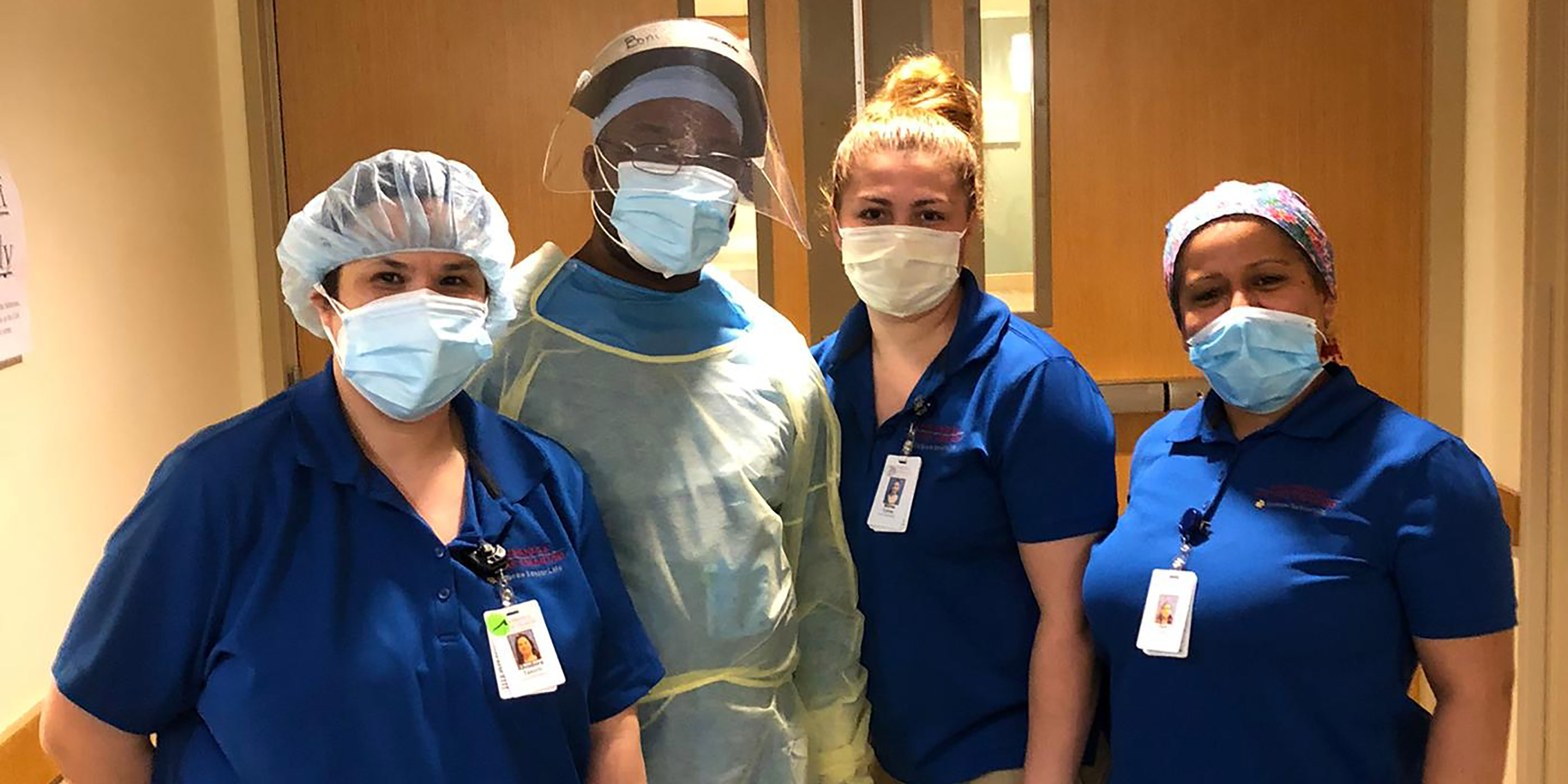 A group of Hebrew SeniorLife staff members stand together while wearing their PPE.