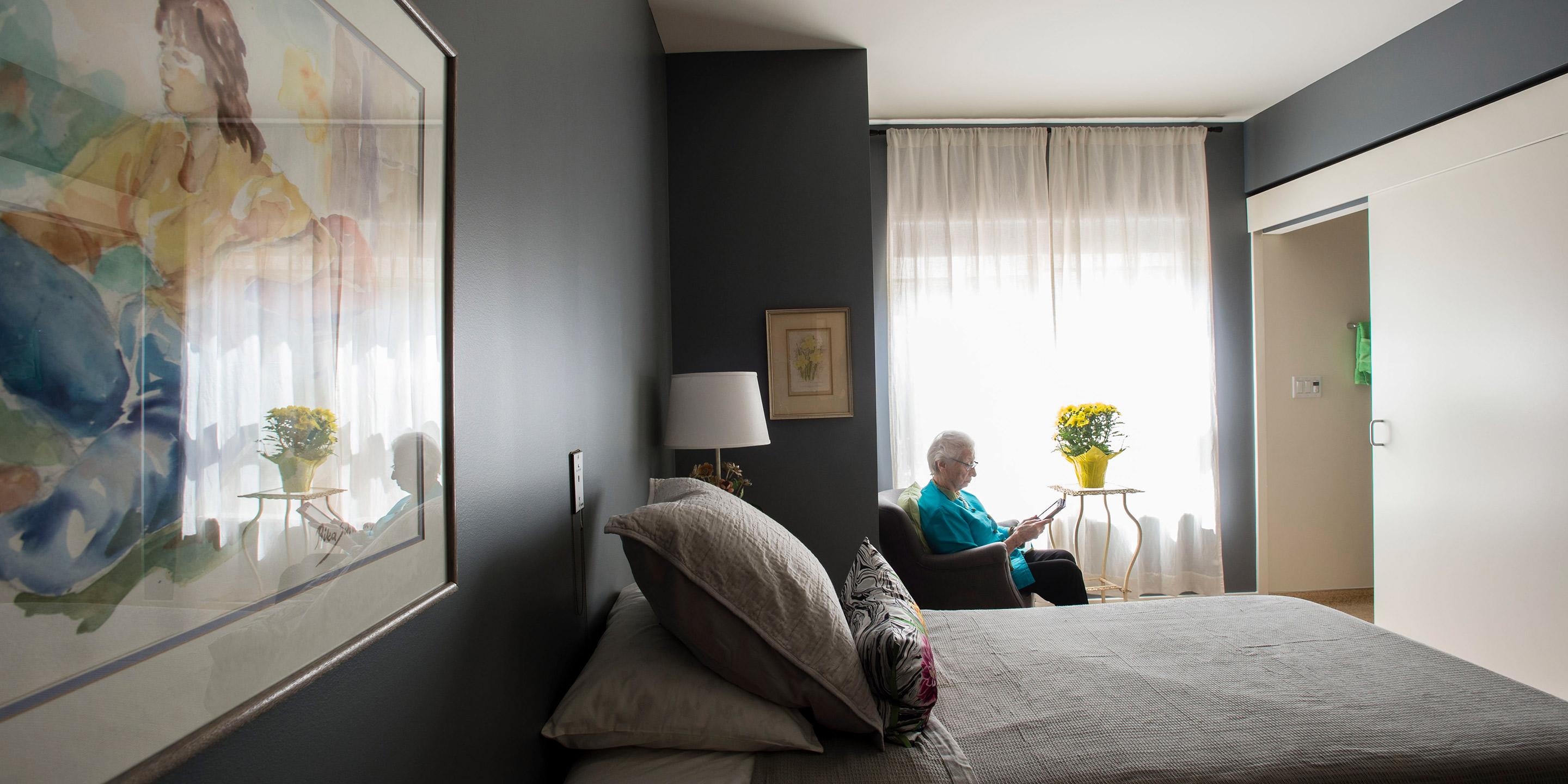 An older adult woman sits in a chair by the window in her room and reads