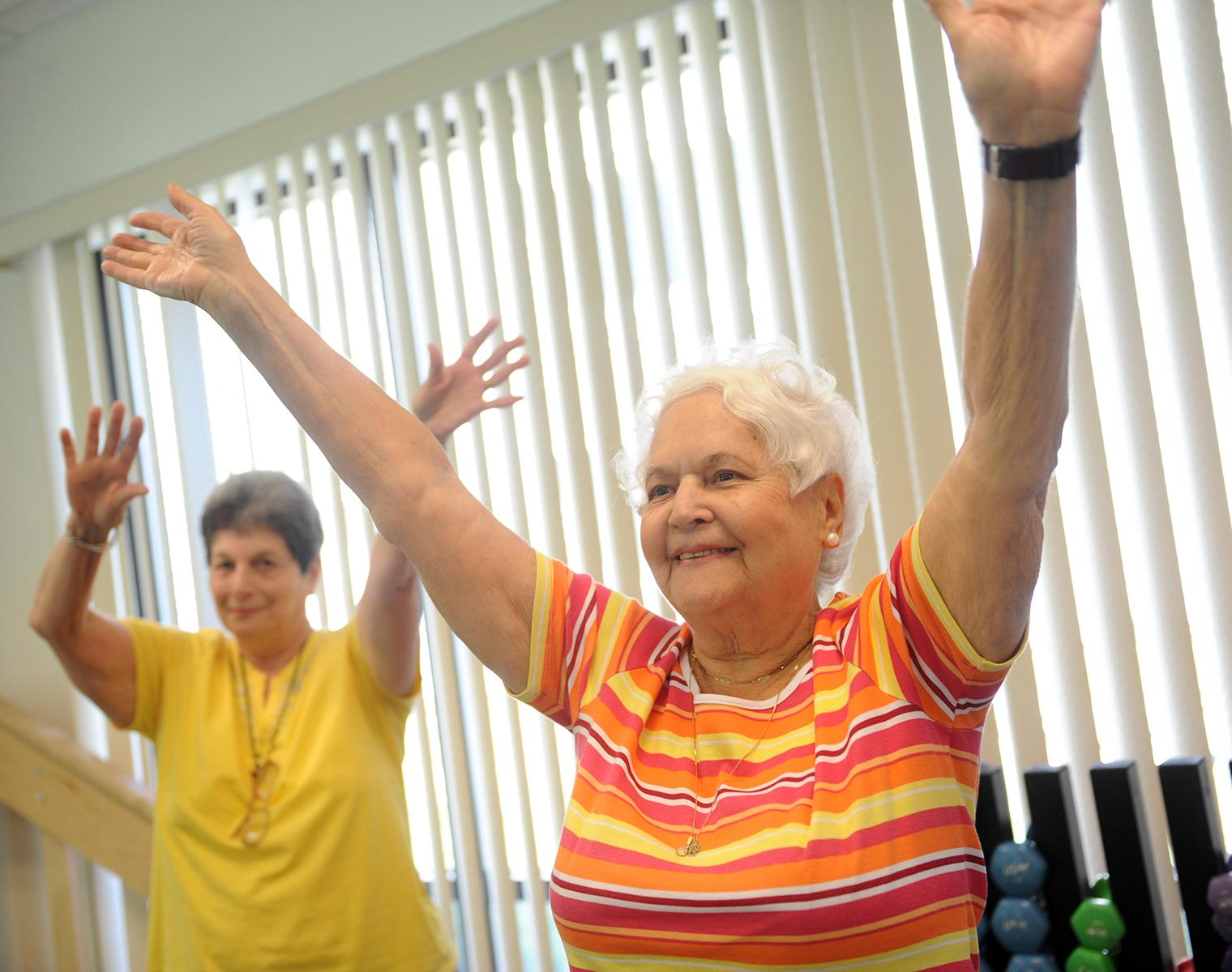 Two smiling older women, one in the background and one in the foreground, hold their arms in the air. Behind them is a wall of windows and a weight rack with dumbells.