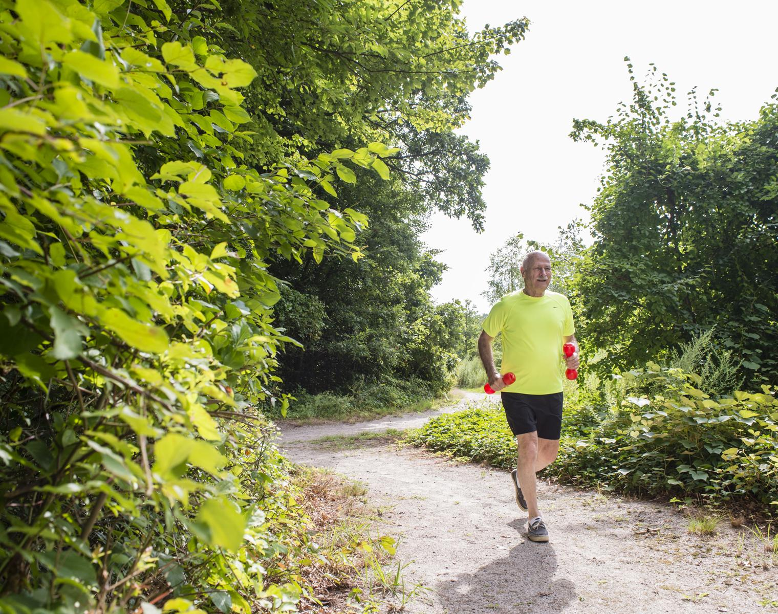 A resident of NewBridge on the Charles jogs with hand weights through one of the wooded trails that surround the community.