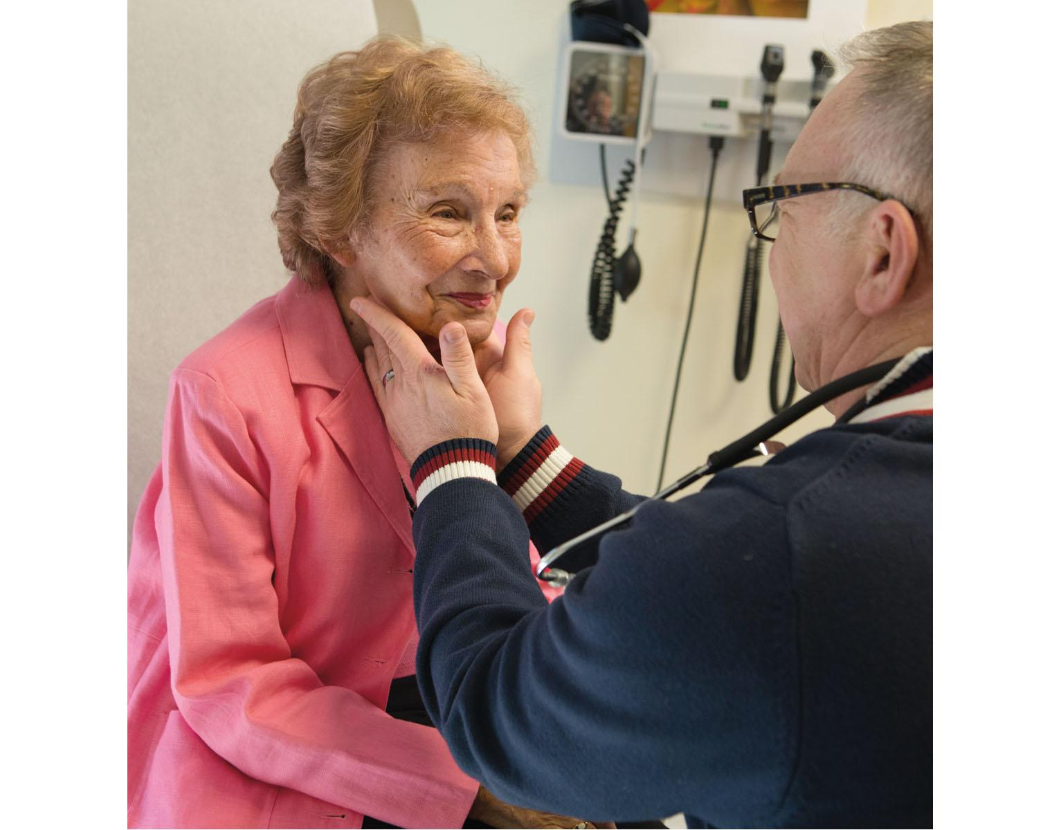 Older adult in pink sweater interacts with a doctor during a visit.
