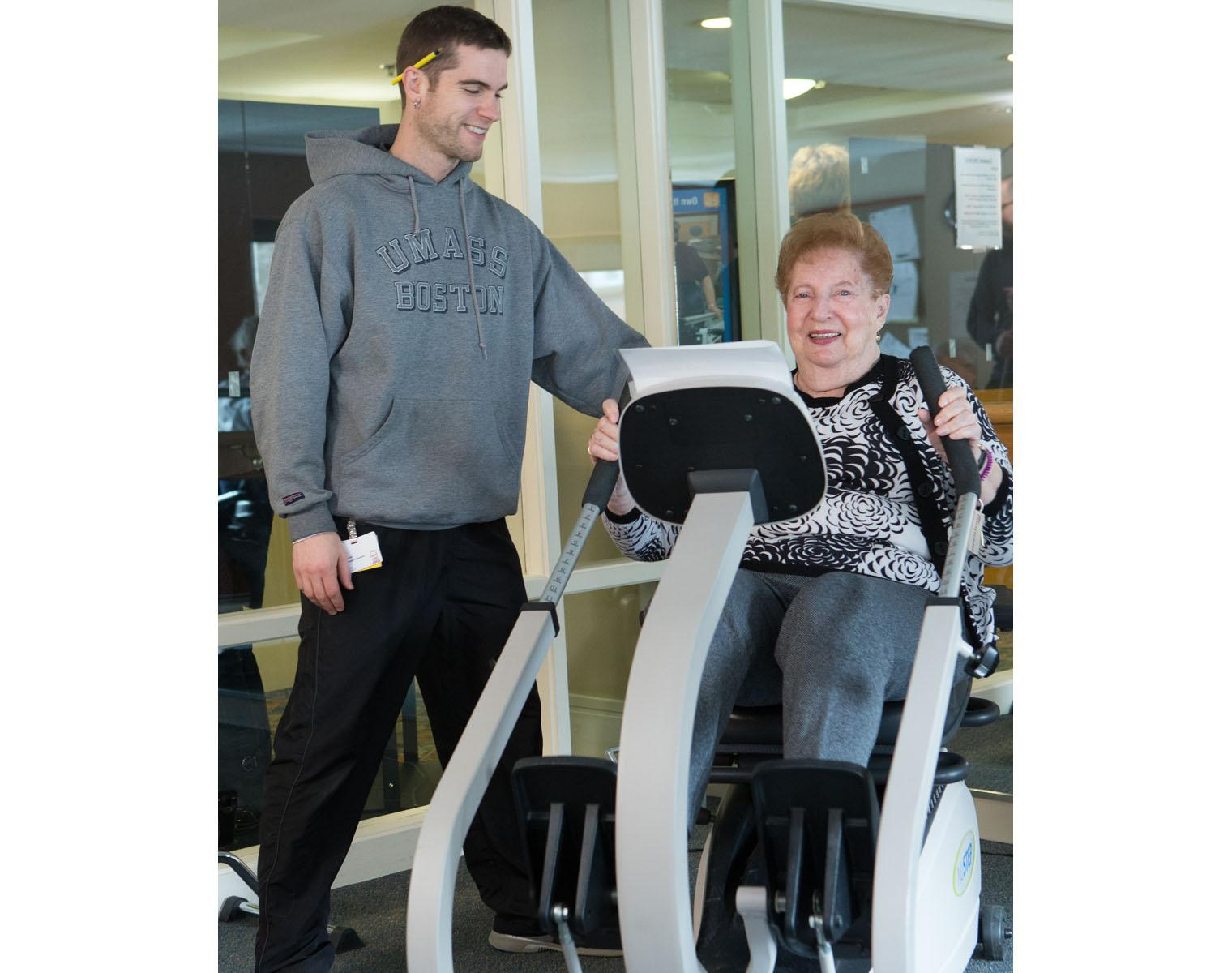 A resident uses specialized fitness equipment for seniors as an exercise instructor looks on.