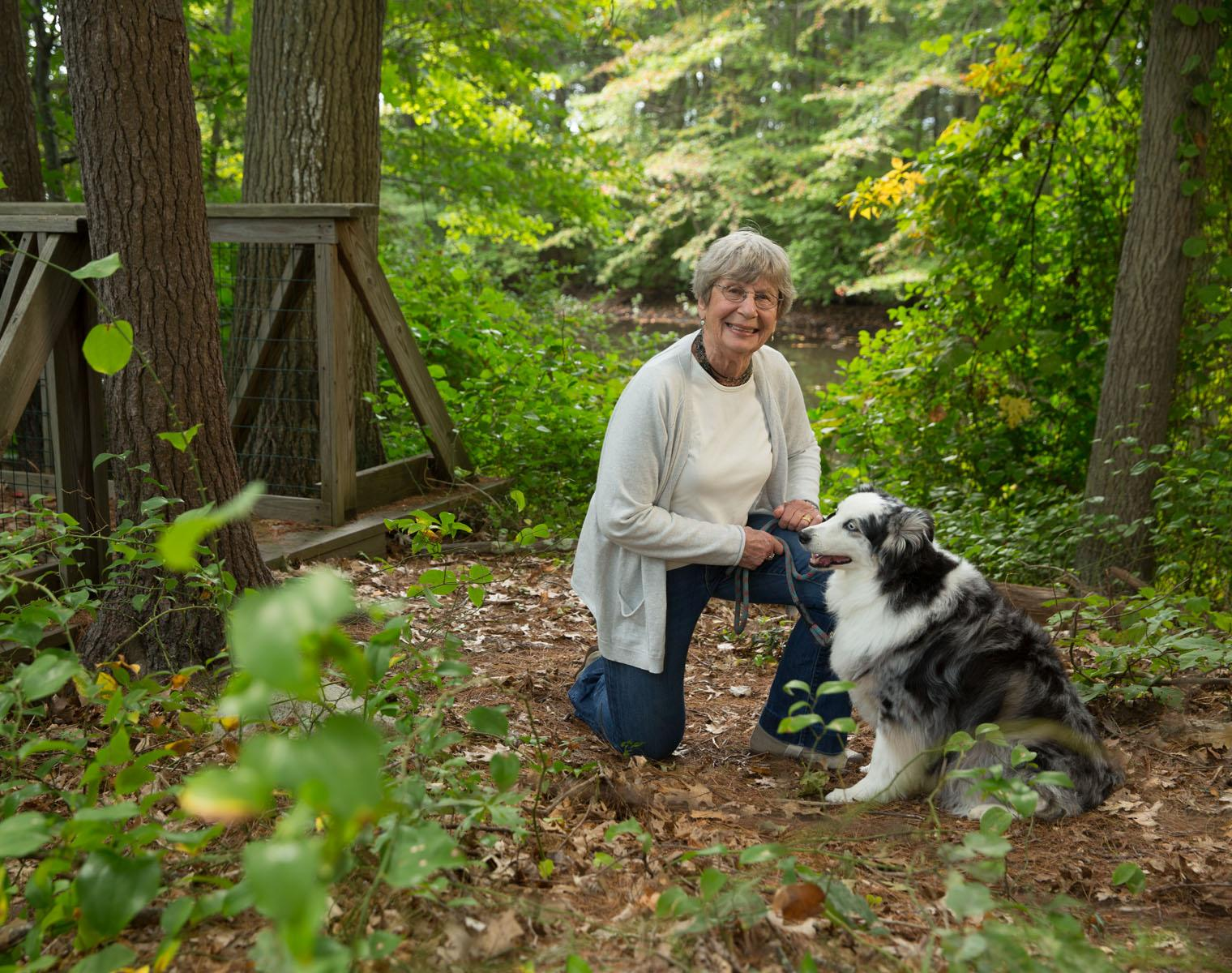 An Orchard Cove resident walks her dog on one of the many wooded trails surrounding the community.