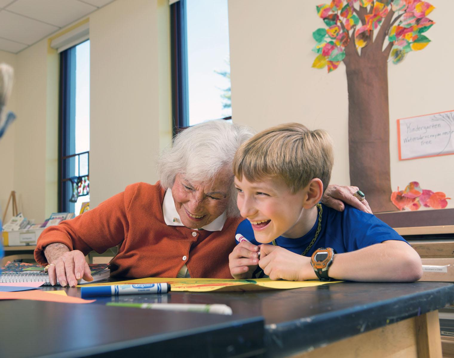 An older with and a school age boy laugh together while working on an art project.