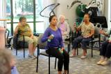 A female fitness instructor leads a group of seniors in a group fitness class involving weights.