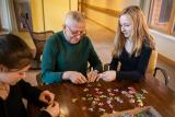 Two young girls sit with an elder man around a table and work on a puzzle together.
