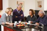 Four residents stand around a kitchen island and talk over coffee