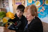 A resident in memory assisted living at NewBridge on the Charles in Dedham, MA arranges flowers with a middle-school aged student.