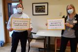 HSL employees Matt Hollingshead and Kim Brooks hold up signs saying why they received their COVID-19 vaccines.