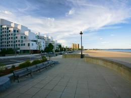 On the left, a white apartment building about eight stories high sits in front of Revere Beach Boulevard. On the right, we see the ocean and a beach, with benches and a sidewalk running alongside.