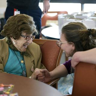 An older woman sits at a table and smiles as she is greeted by a younger woman.