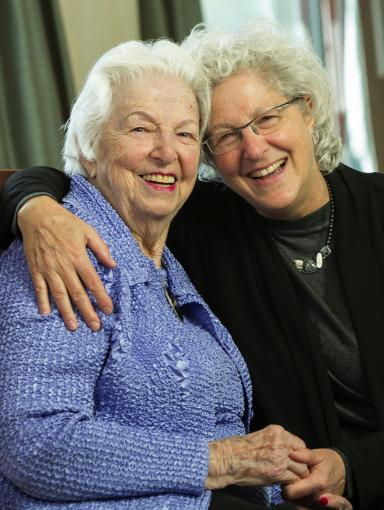 Two women embracing and holding hands, smiling at the camera.