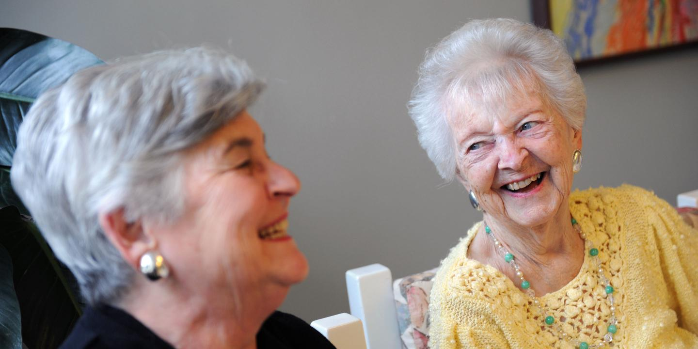 Adult daughter laughs with her mother, a long-term chronic care patient at Hebrew Rehabilitation Center