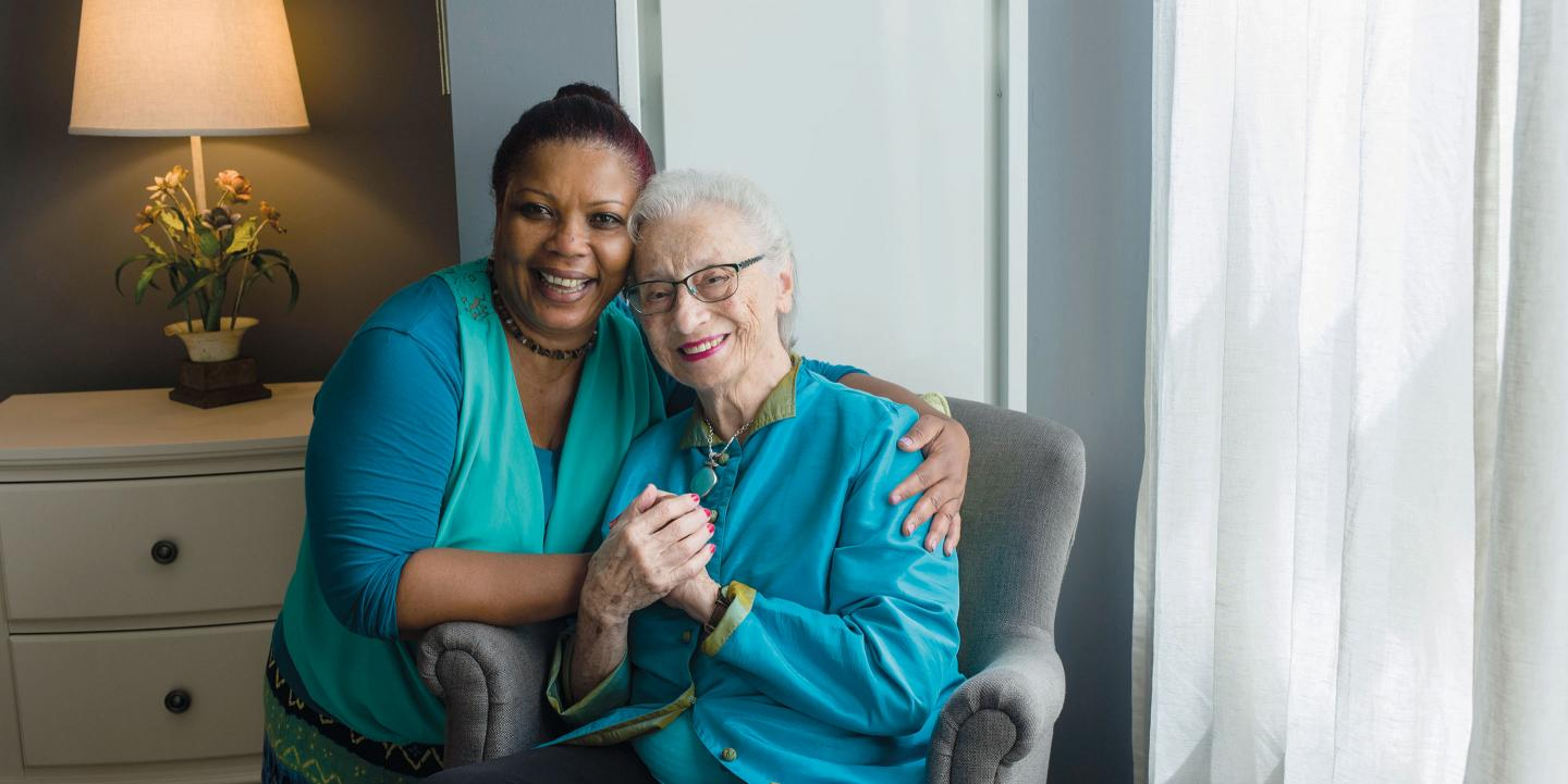 A memory care assisted living resident spends time with a beloved team member in her apartment at NewBridge on the Charles.
