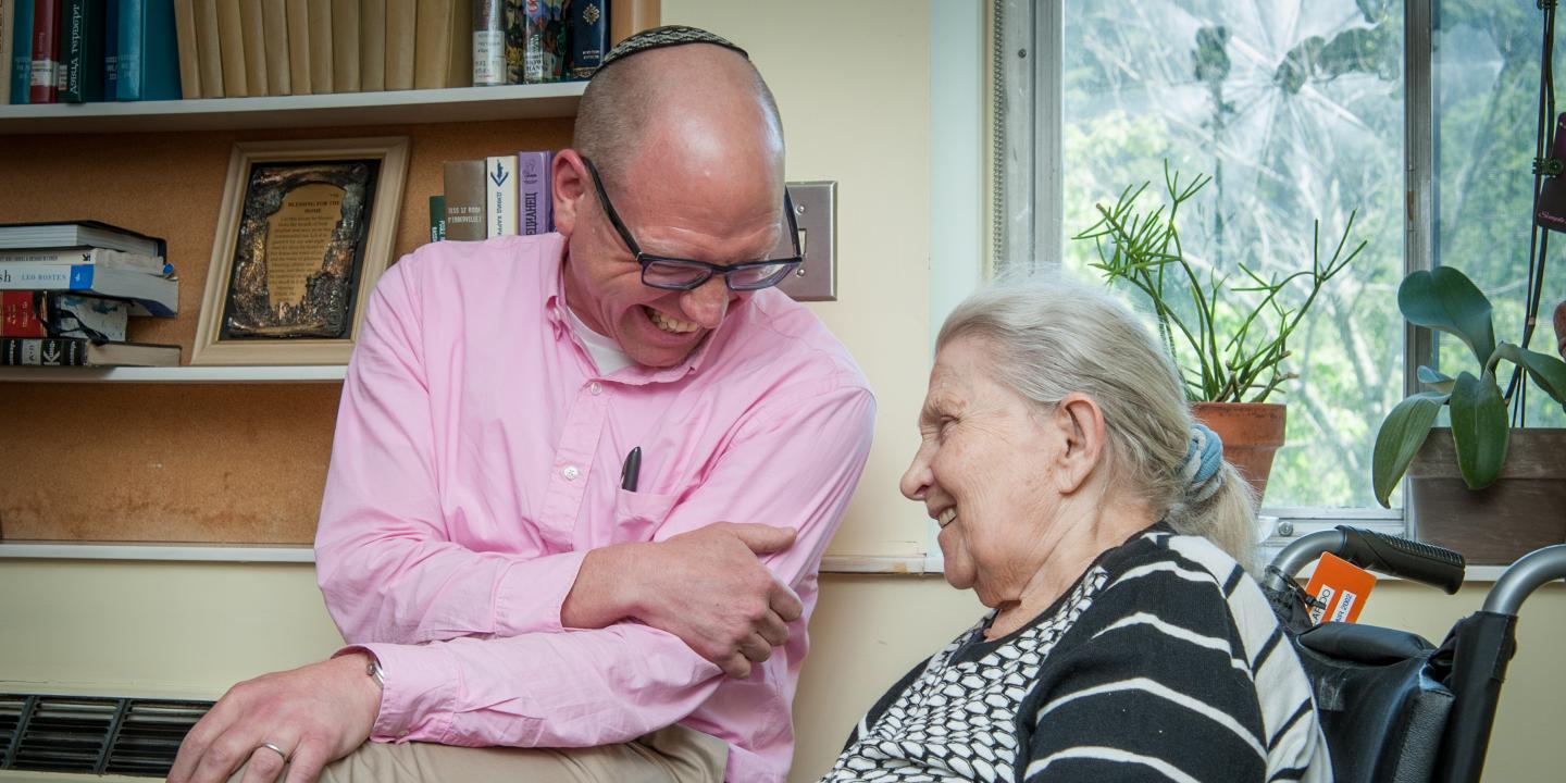 A man wearing a yarmulke sits with an older female Hebrew Rehabilitation Center patient in a wheelchair. They are both smiling and leaning in toward each other.