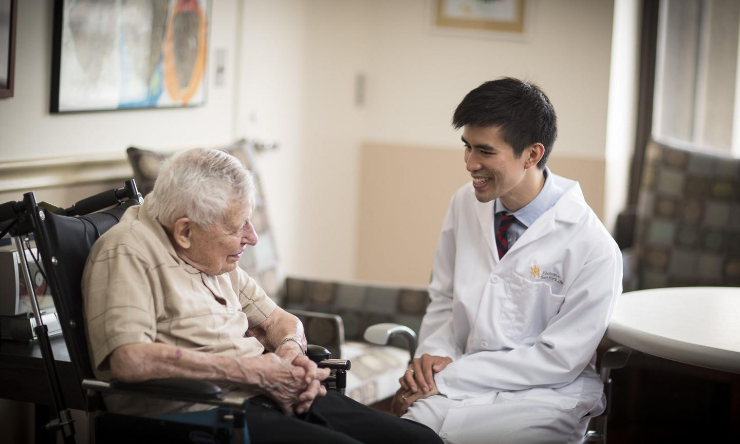 An older man in a wheelchair sits talking with a young Harvard Medical School doctor at Hebrew SeniorLife. The doctor is smiling and wearing a white coat.