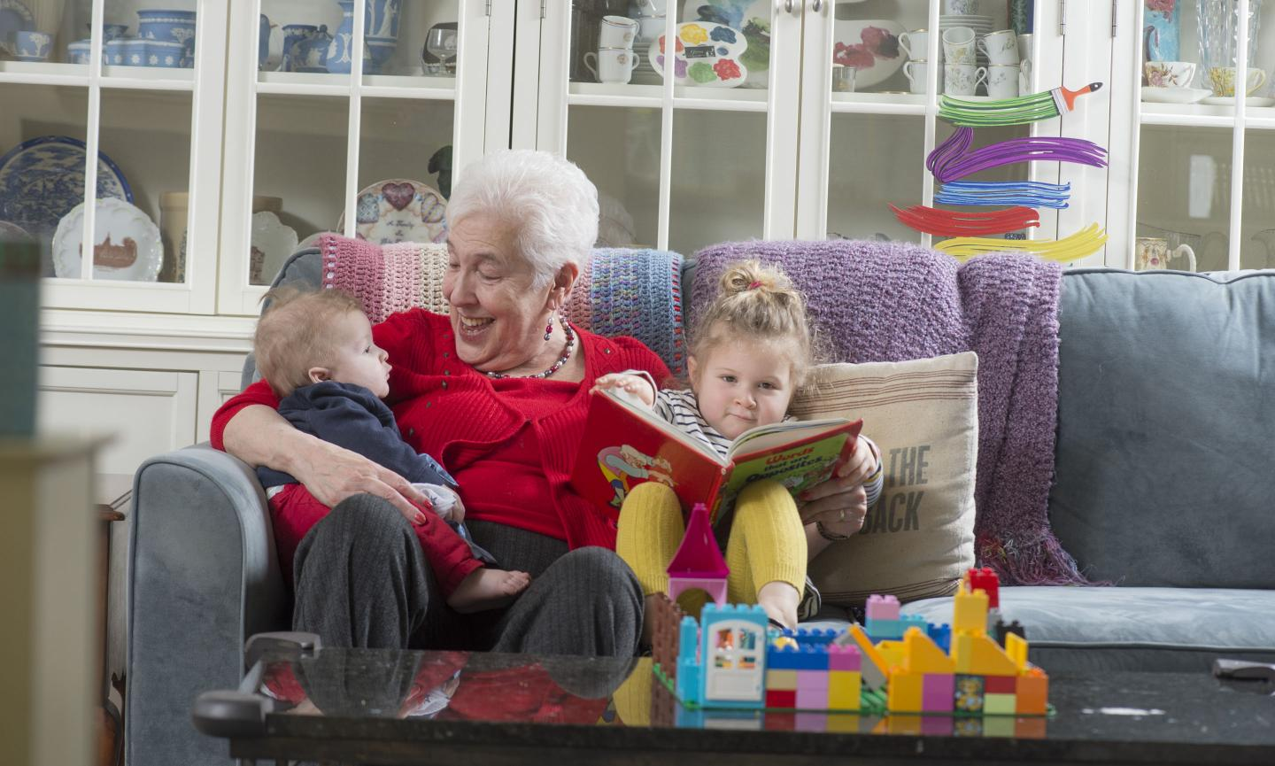 Grandmother in red sweater sits on couch with two grandchildren, a baby under one arm and a toddler with a book under the other. Brightly-colored blocks sit on a coffee table.