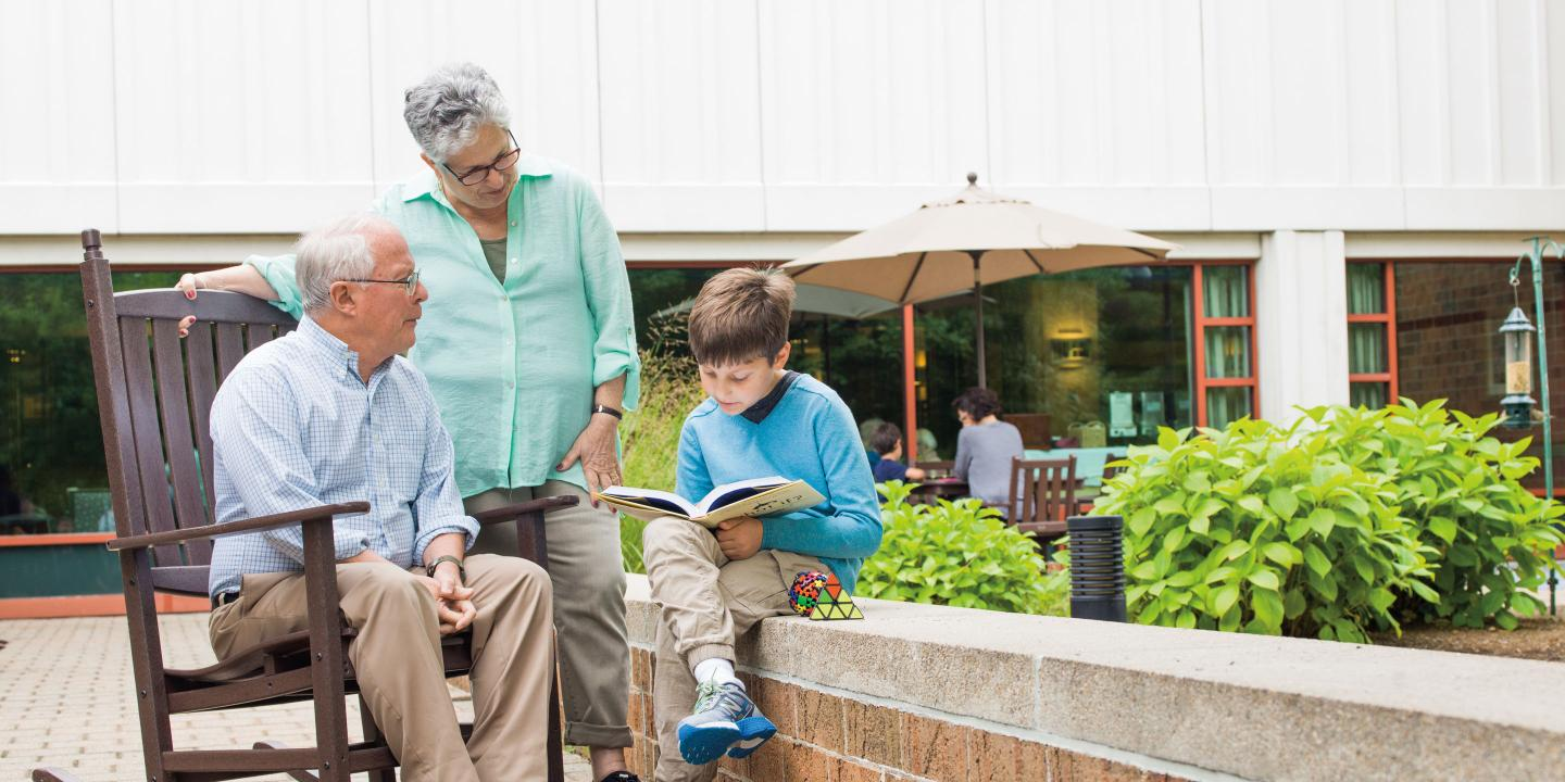 Grandparents spend time reading with a grandchild in the courtyard of a Hebrew SeniorLife senior living community.