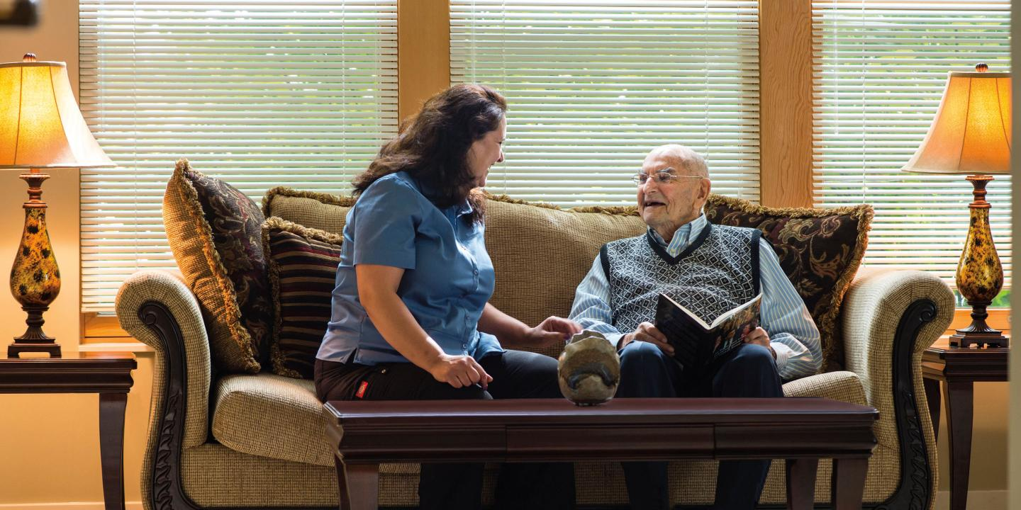 An assisted living resident of NewBridge on the Charles chats with his certified nursing assistant in the living room of his spacious apartment.