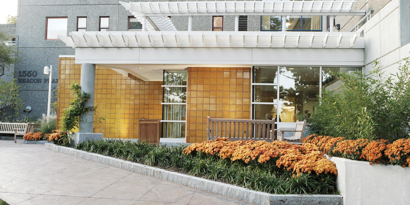 A path lined with orange flowers and green shrubs leads to the entrance of 1550 Beacon Street, part of Center Communities of Brookline.