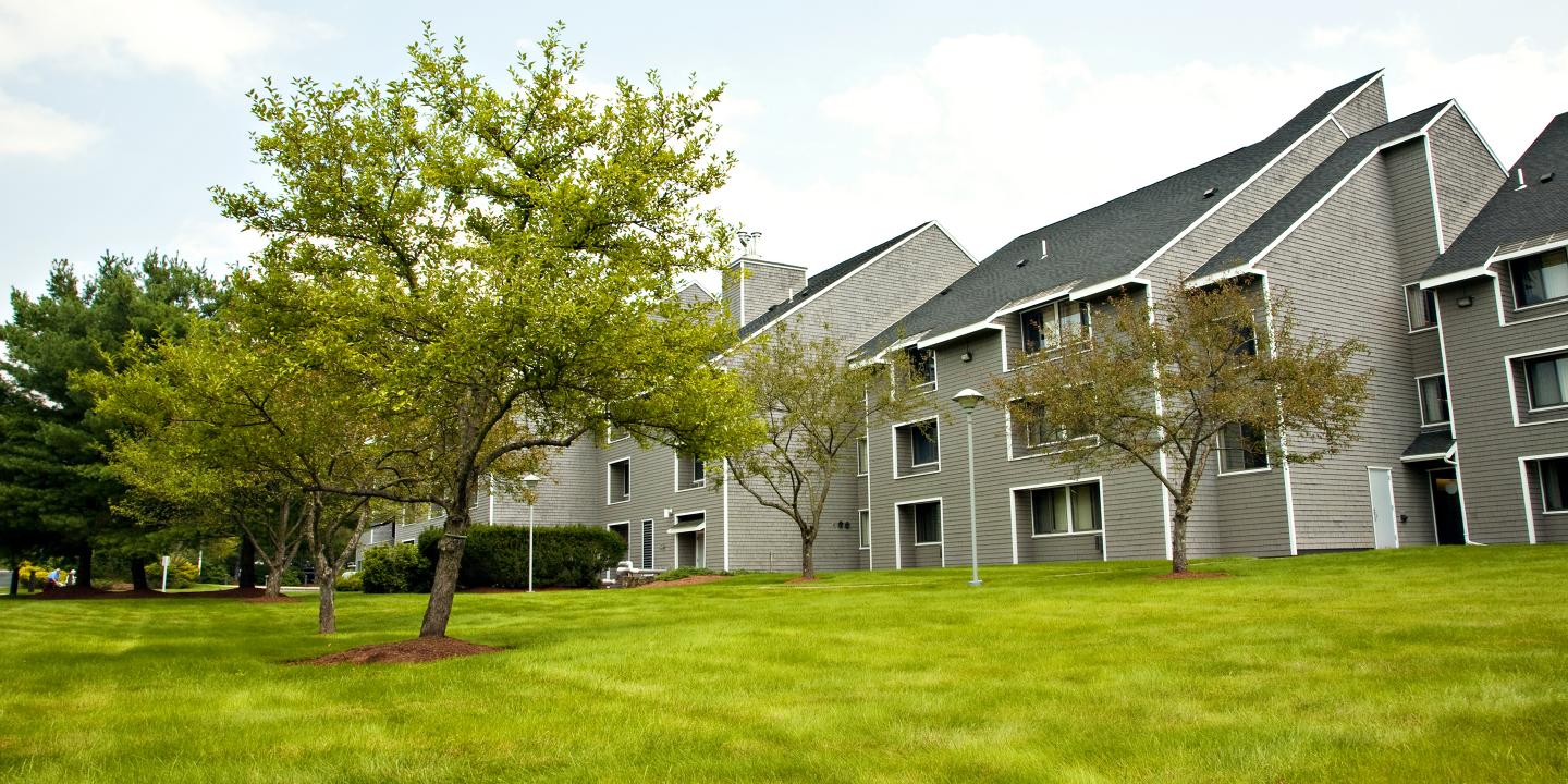 Exterior shot of three-story apartment complex surrounded by trees and grass.