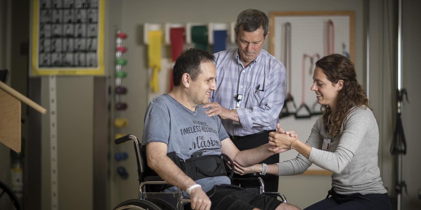 A physical therapy patient in a wheelchair in a gym at Hebrew Rehabilitation Center in Boston. A physical therapy student is crouched next to him, holding his arm and elbow. A physical therapist stands behind with his hand on the man's shoulder.