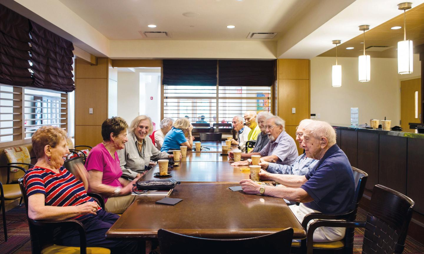 A group of NewBridge residents enjoy coffee and conversation following a theatrical performance in Great Meadow Hall.