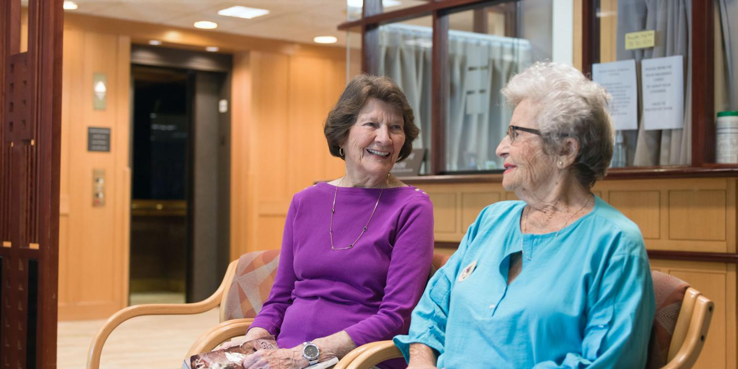 Two residents of Orchard Cove chat in the waiting area of the community's Harvard Medical School-affiliated medical practice.