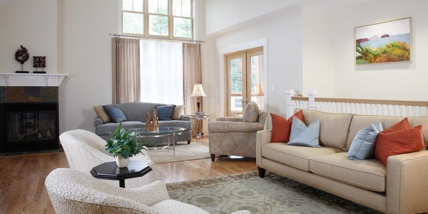 This spacious, sunny, and well-decorated living room with two seating areas is a typical independent living residence interior at NewBridge on the Charles.