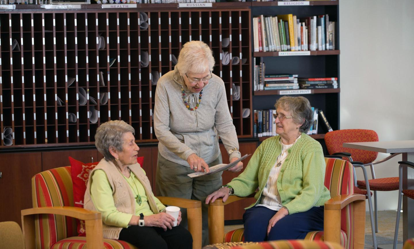 Three women drink coffee and converse in a library seating area at Center Communities of Brookline