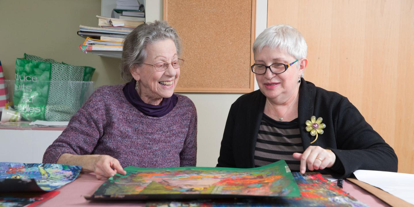 Two residents of Center Communities of Brookline look at their artwork together.