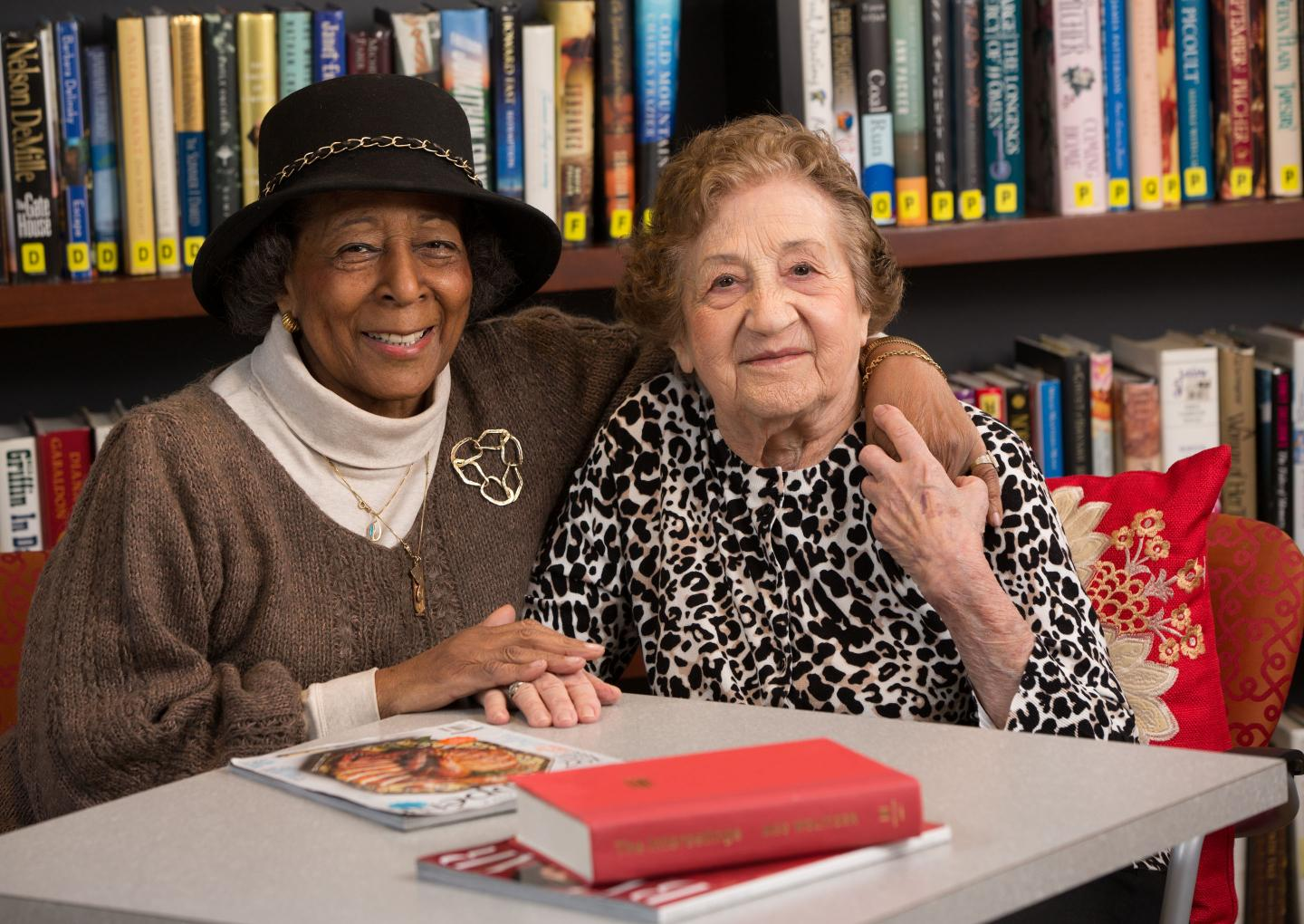Two older women sit together in a library at a table with books and magazines.