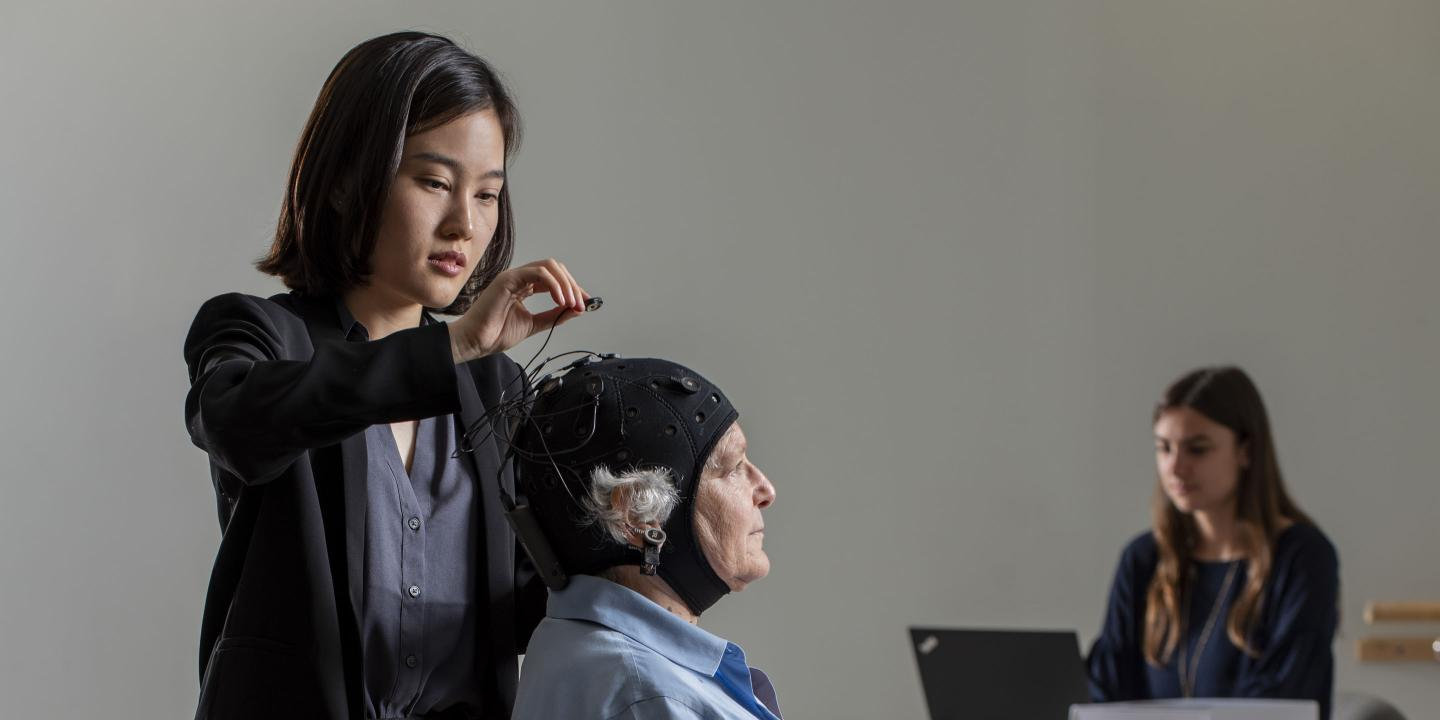 An older woman sits in a chair while a younger woman attaches wires to a black brain stimulation cap the older woman is wearing