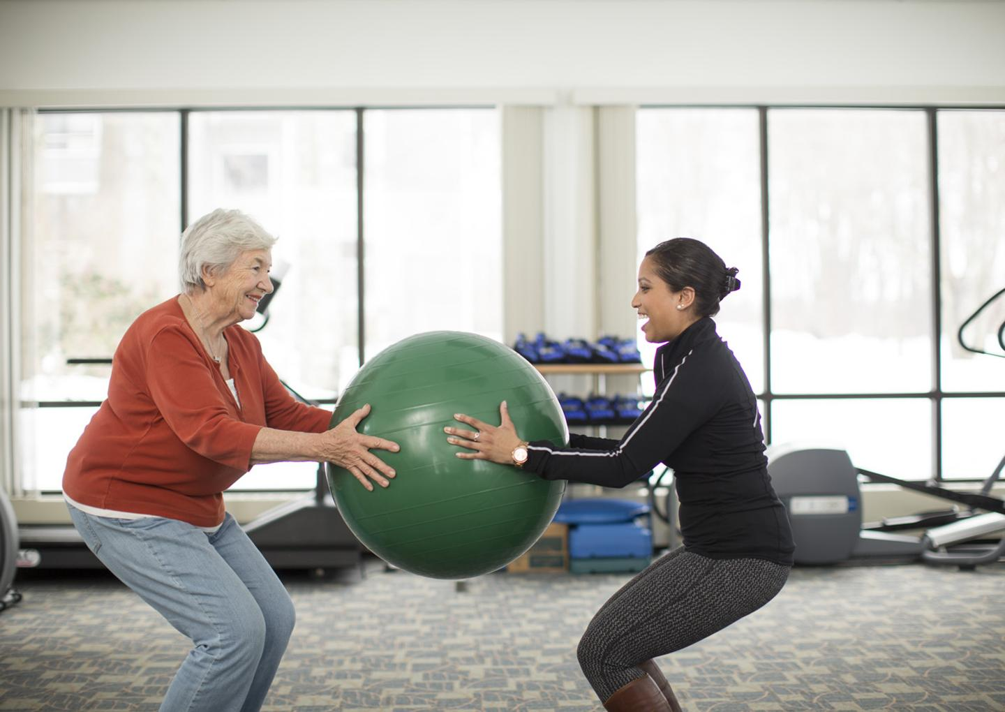 An older woman on the left and younger woman on the right stand facing each other, standing in a squat position, holding a large exercise ball between them. They are in a gym with large windows and exercise equipment in the background.