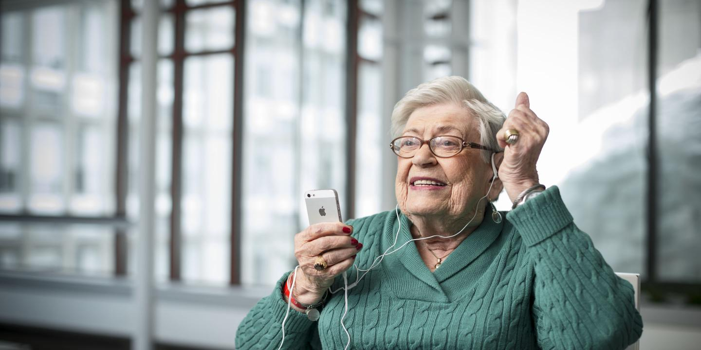 Older woman listens to music on an iPod.