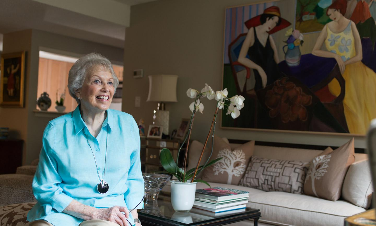 Attractive smiling older woman in a turquoise shirt sits on a couch in her well-appointed independent living apartment.