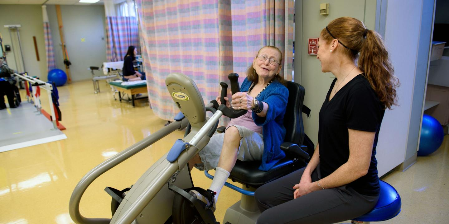Physical therapist observes as an older woman uses a stationary bike in rehabilitation gym