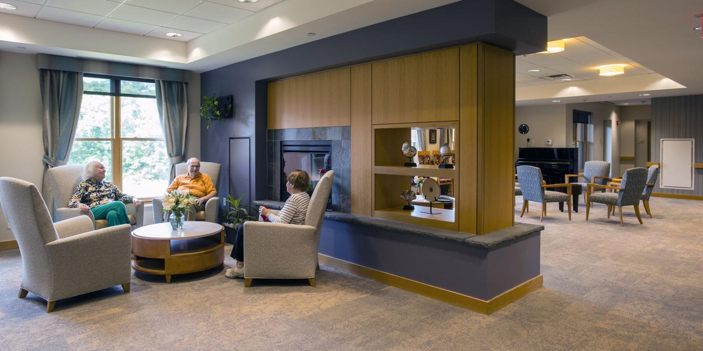 Three residents of Memory Care Assisted Living at NewBridge on the Charles enjoy a conversation in one of our spacious common areas, featuring contemporary décor and plenty of natural light.