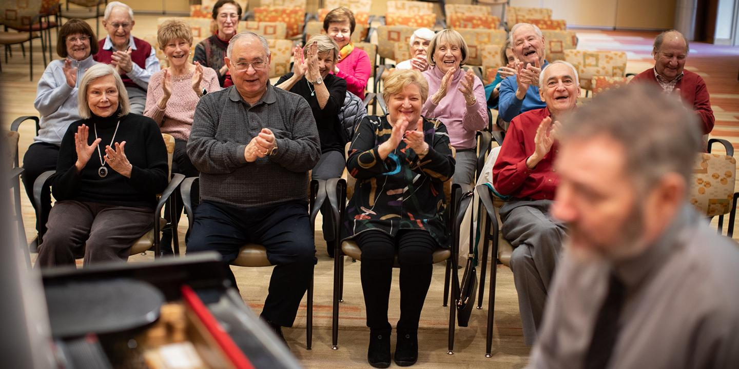 A crowd of seniors enjoy a live performance in Great Meadow Hall.