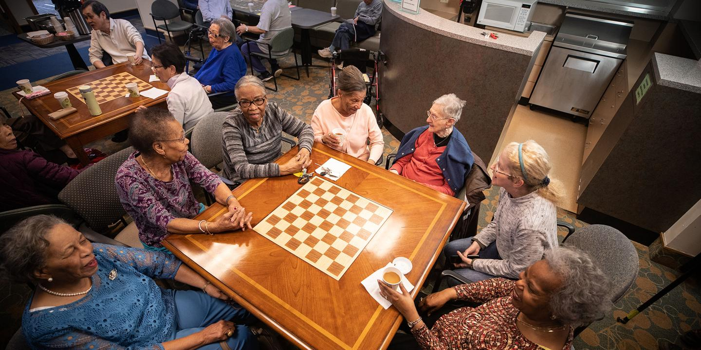 A diverse group of seniors sits at a table, laughing and chatting at Simon C. Fireman Community in Randolph, MA