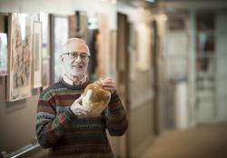 An older bearded man in a multi-color sweater standing in a hallway gallery at Orchard Cove holds a ceramic pot he has made.