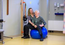 A man on exercised on a balance ball with a therapist assisting.