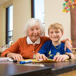 Older woman sits with her arm around a young boy as they work on an art project together.
